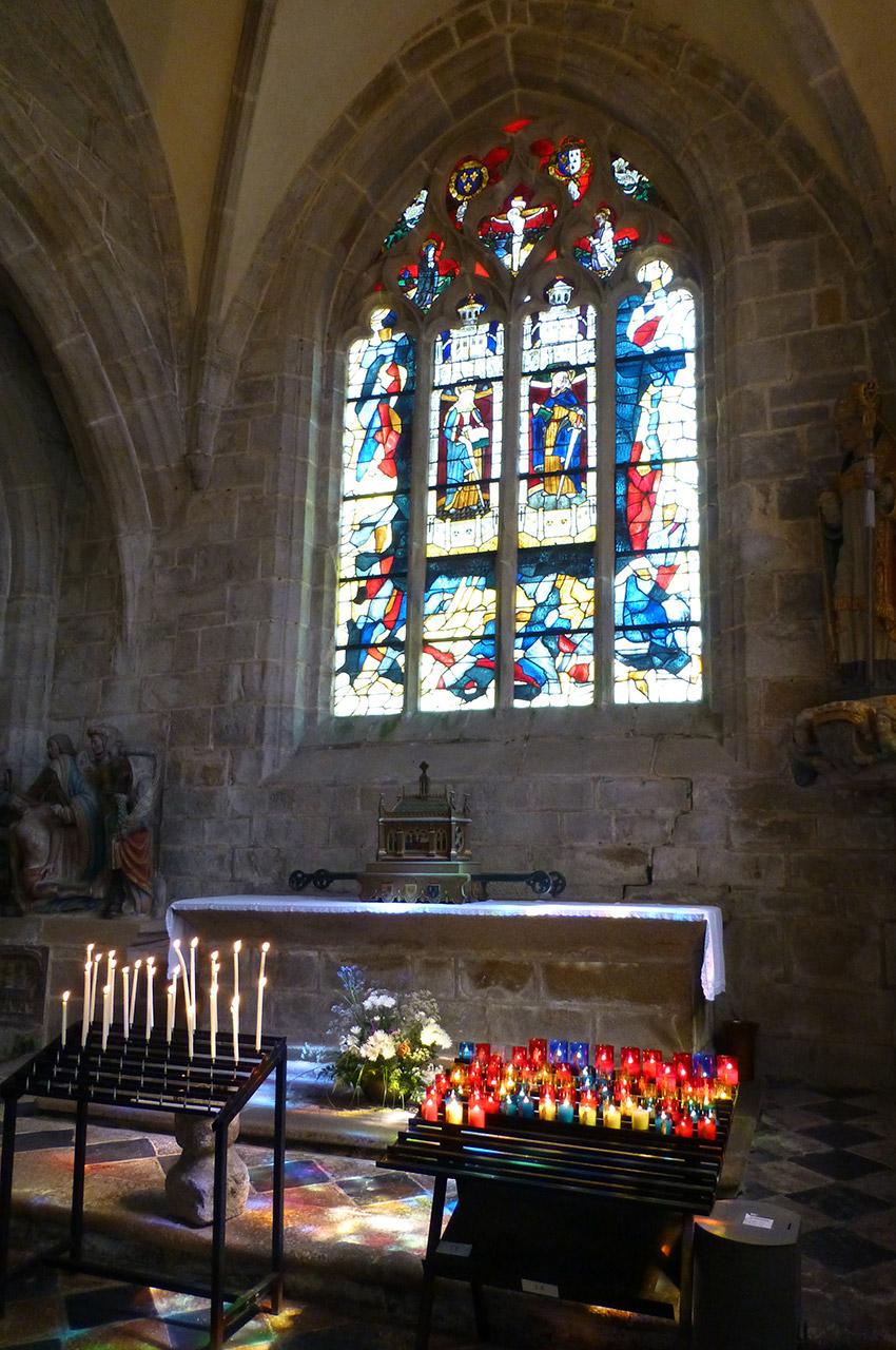 Bougies et vitraux dans l'église Saint-Ronan
