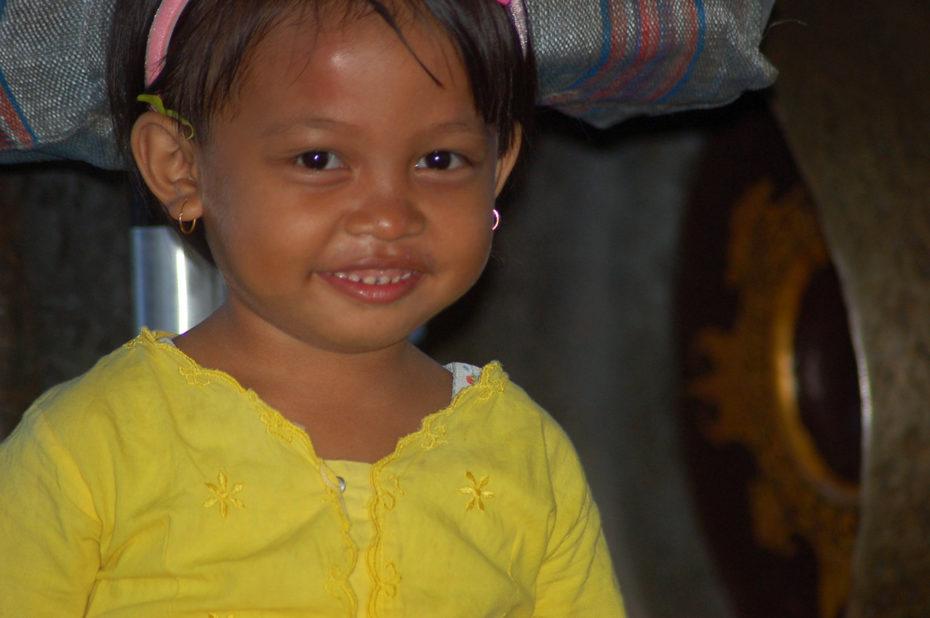 Une petite fille sourit à l'objectif