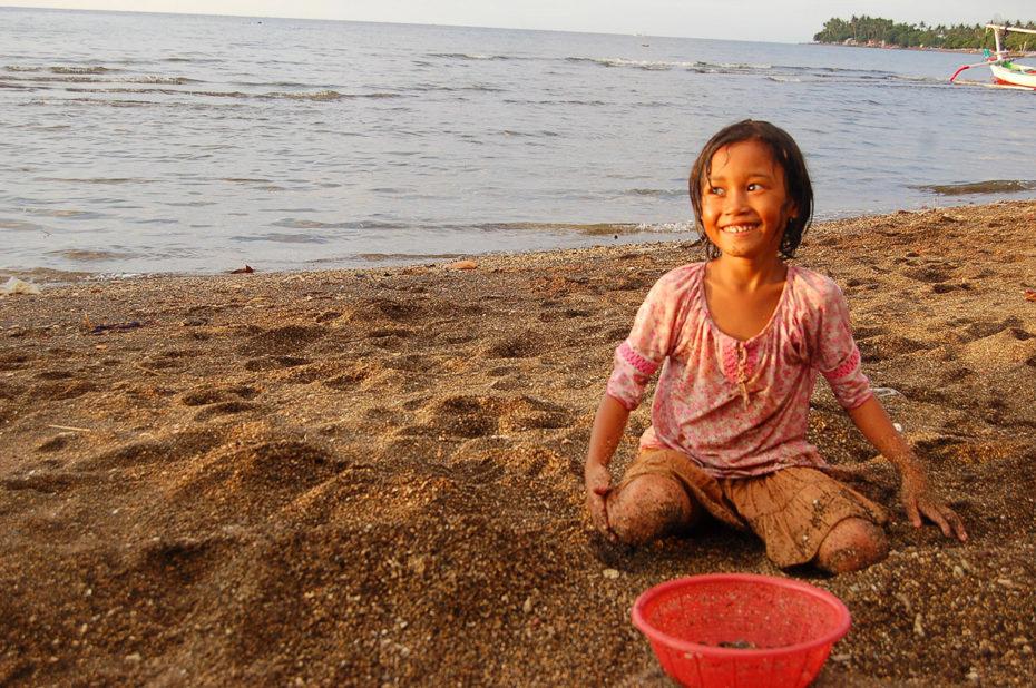 Petite fille ramassant des coquillages