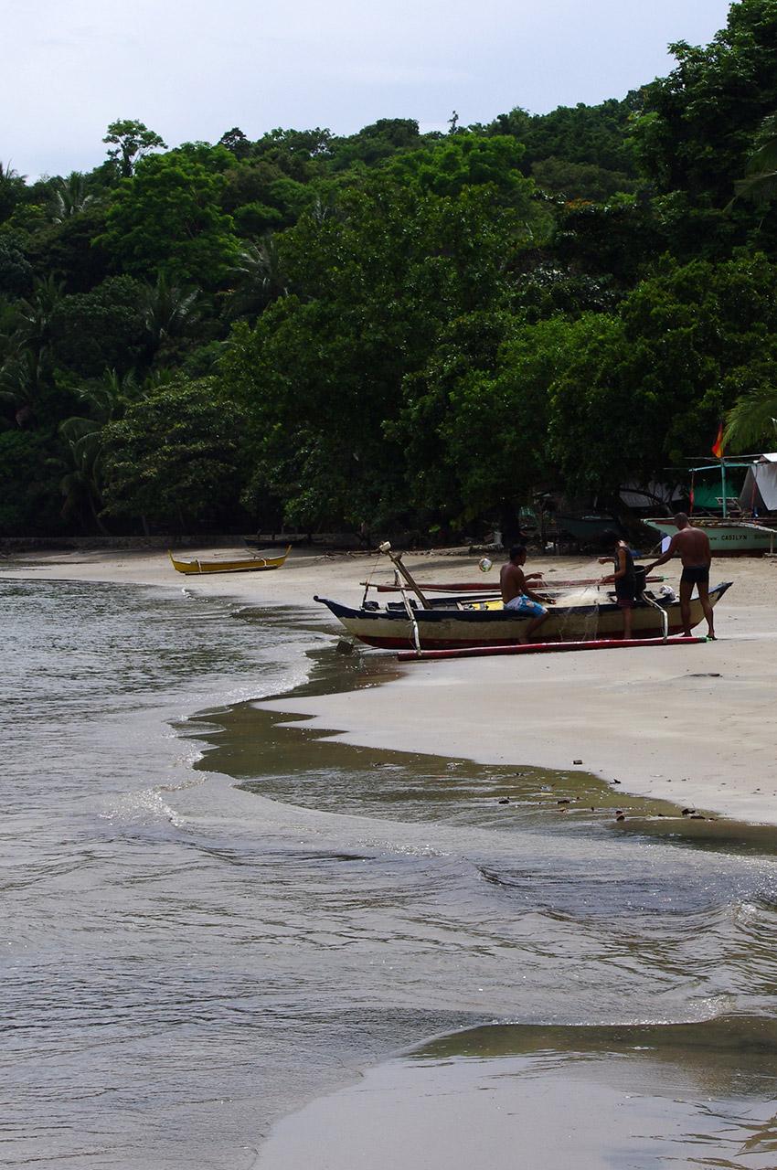 Trois hommes démêlant les filets de pêche