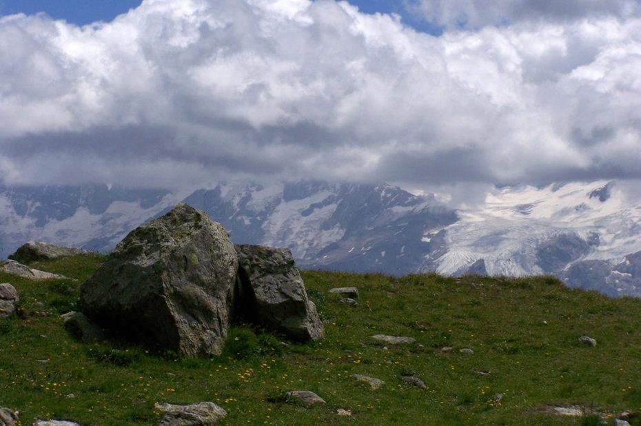 Des nuages blancs s'accrochent aux sommets des Écrins