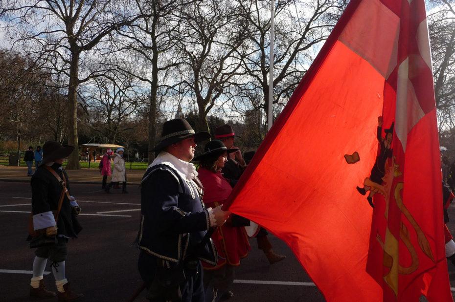 Des figurants portant un drapeau rouge au défilé