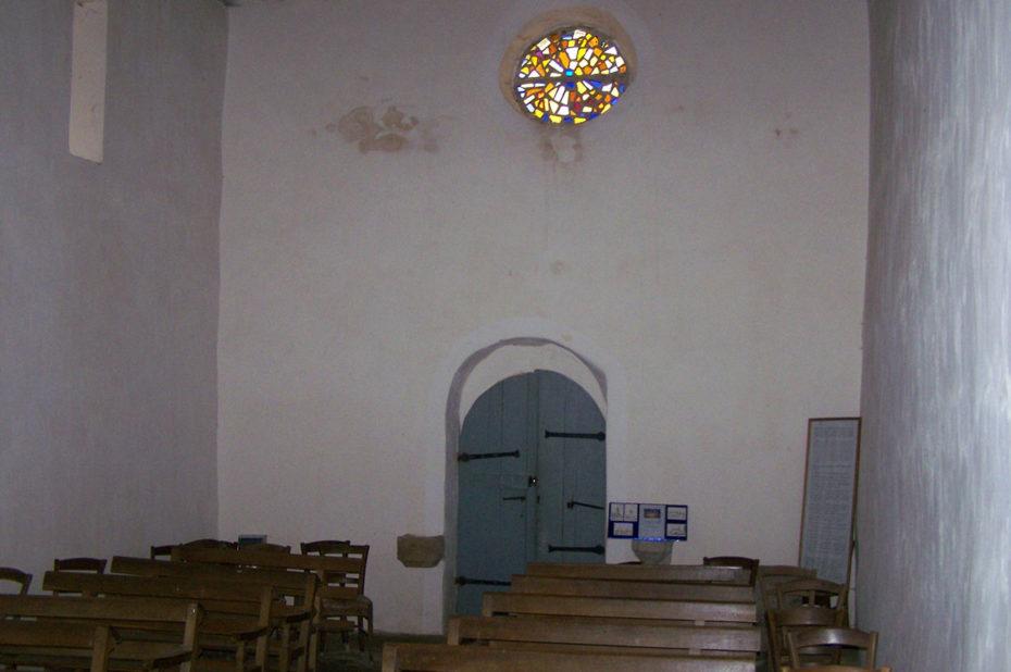 Les bancs et la porte d'entrée de la chapelle