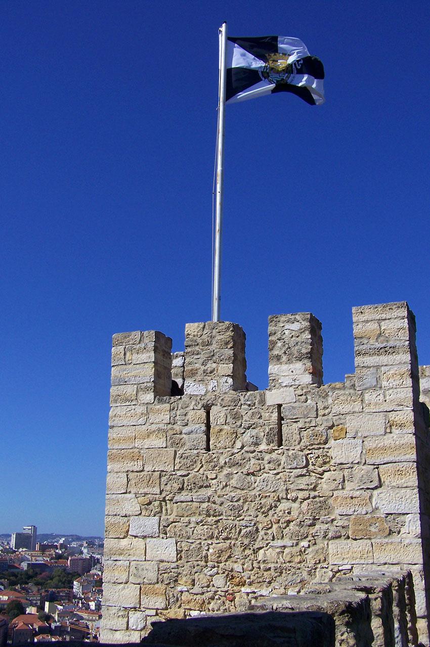 Drapeau, créneaux et la ville de Lisbonne en contrebas