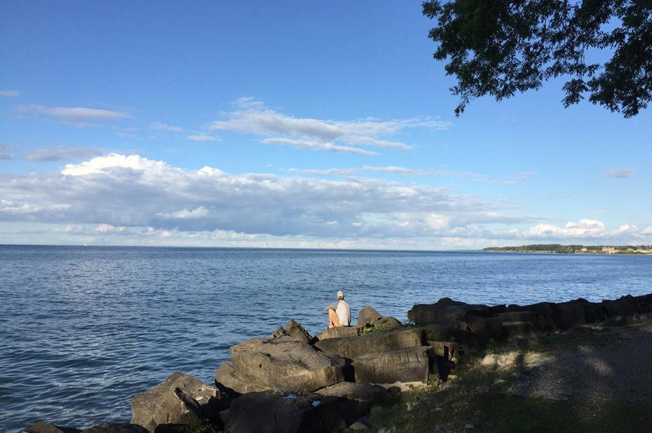 Un homme assis au bord du lac Ontario