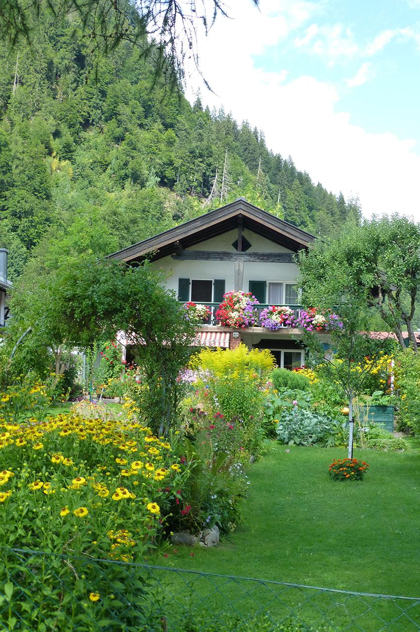 Chalet caché par la végétation et les massifs de fleurs
