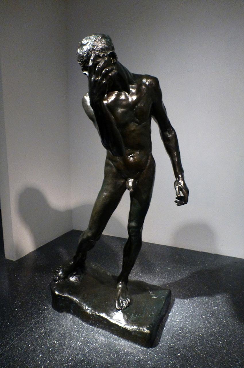 Statue de bronze d'un homme se masquant le visage