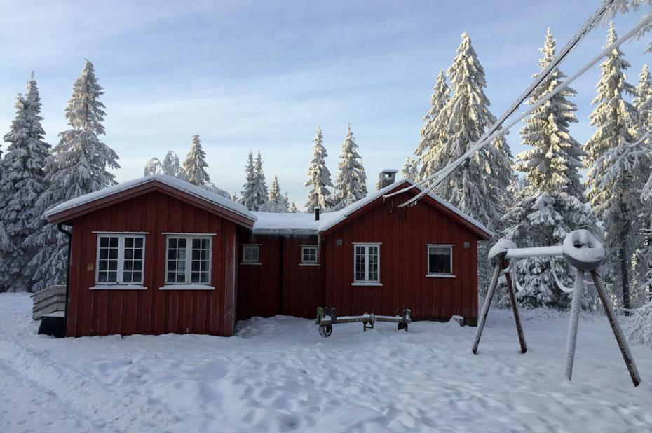 Petite maison rouge en bois dans la neige