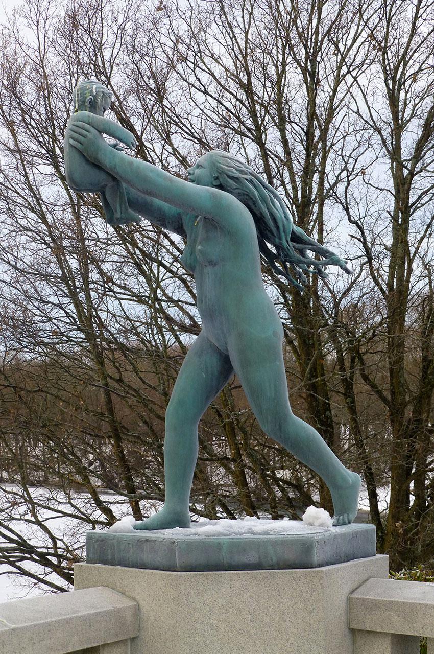 Statue d'une femme portant son enfant à bout de bras