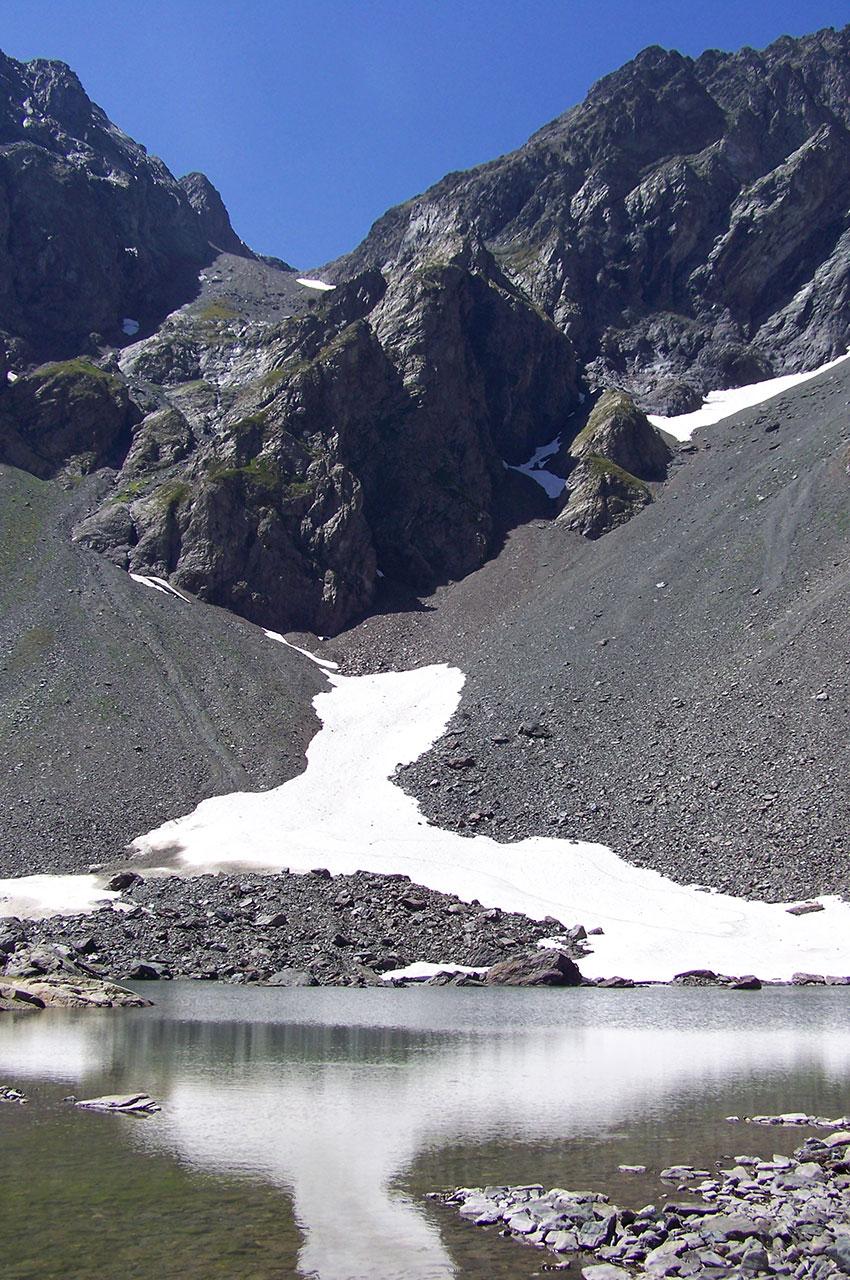 Un névé se reflète sur le lac de Belledonne