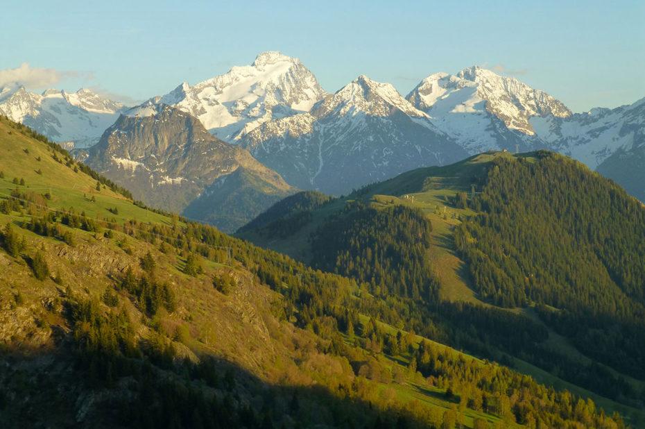 Sommets enneigés et jeux de lumière sur la vallée verdoyante