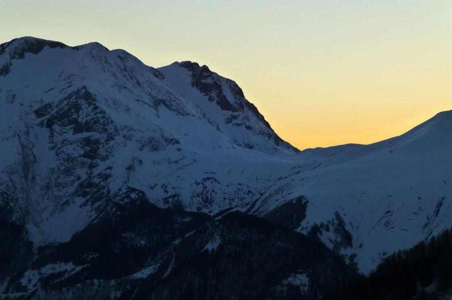 Magnifiques teintes orangées du soleil se couchant derrière la montagne