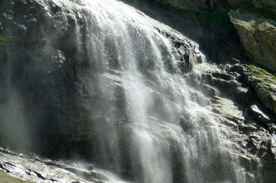 Les fines gouttelettes d'eau de la cascade scintillent au soleil