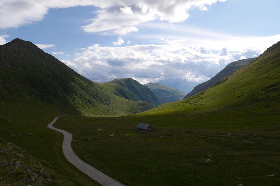 La route de Sarenne descend dans la vallée dans un jeu d'ombres et de lumières