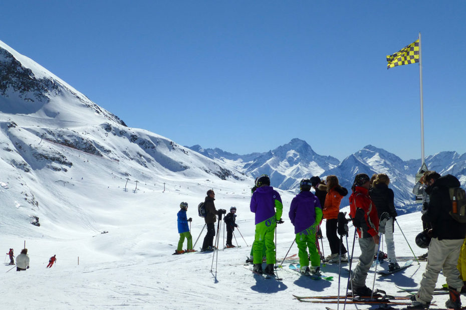 Un groupe de skieurs attend en haut des pistes