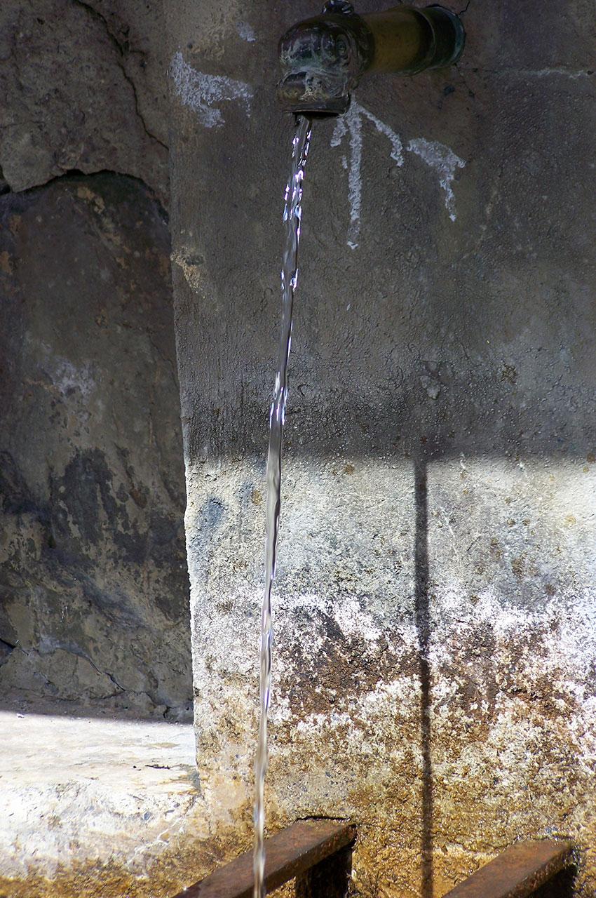 Filet d'eau sortant d'une fontaine à Vénosc